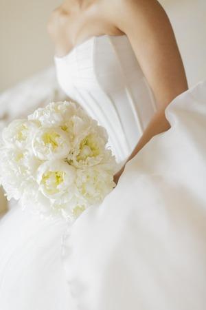 Sposa sul vestito bianco con il fiore bianco