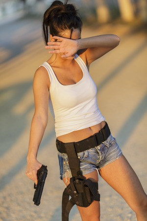 weaponry: Young woman with a gun Stock Photo