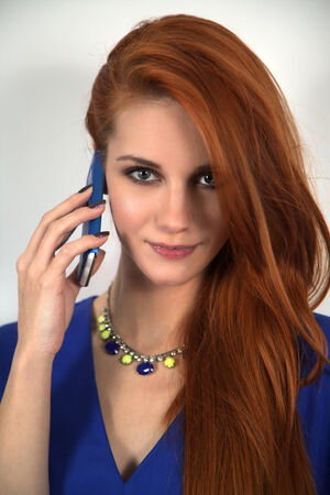 Red hair woman with mobile phone photo