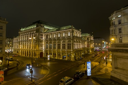 VIENNA, AUSTRIA - FEBRUARY 5, 2014: Unidentified people in front of Vienna State Opera at night. Vienna State Opera was completed in 1869 in the Neo-Renaissance style.