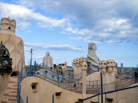 BARCELONA, SPAIN - SEPTEMBER 9, 2014: Unidentified people on the roof of Casa Mila in Barcelona, Spain. Casa Mila is modernist building, built between 1906 and 1910 and designed by catalan architect Antoni Gaudi.
