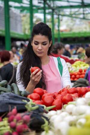 Pretty young woman buying vegetables on the market photo