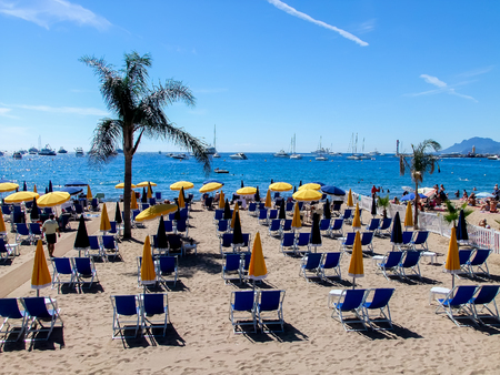 sunbeds: CANNES, FRANCE - SEPTEMBER 12, 2010: Unidentified people at the beach in Cannes, France. Cannes s a busy tourist destination and host of the annual Cannes Film Festival Editorial