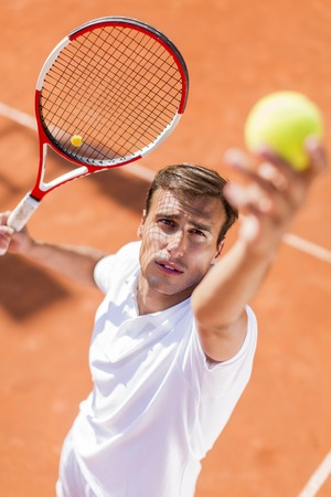 tennis serve: Young man playing tennis Stock Photo