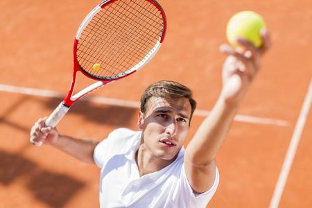 Hombre joven que juega a tenis Foto de archivo - 31048158