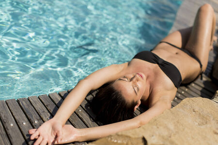Young woman laying by the pool photo