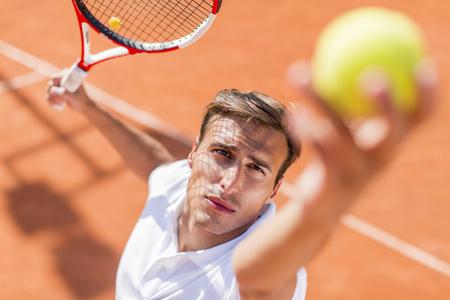 jugando tenis: Hombre joven que juega a tenis