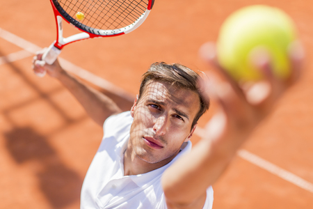 serve one person: Young man playing tennis Stock Photo