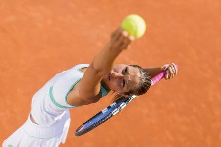 balones deportivos: Mujer joven jugando al tenis Foto de archivo