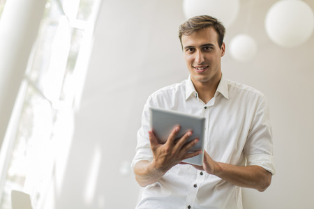 Young man with tablet in the office photo
