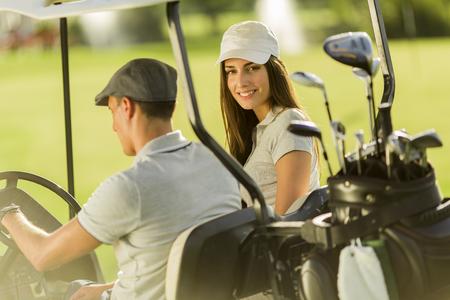 Young couple at golf cart photo
