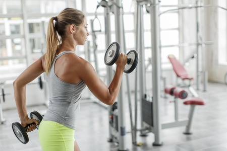 weight machine: Pretty young woman training in the gym