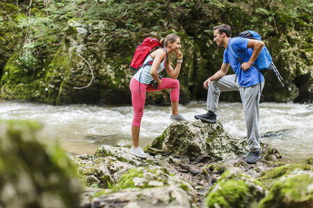 Young couple hiking by the river photo