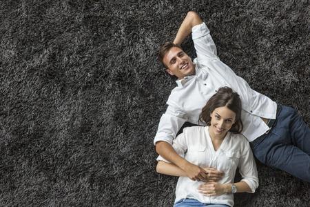 若いカップル、カーペットでリラックス