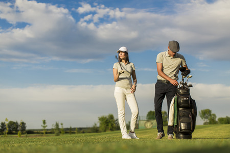 Young couple playing golf photo