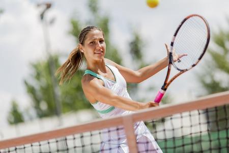 Mujer joven jugando al tenis Foto de archivo
