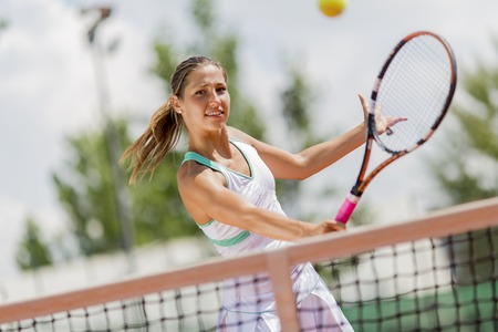 action girl: Young woman playing tennis
