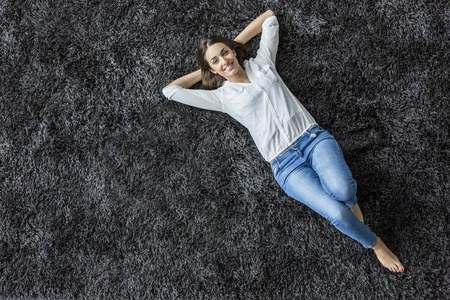Young woman laying on the carpet 版權商用圖片 - 34254604