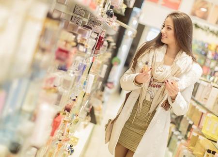 Jonge vrouw in de parfumerie Stockfoto