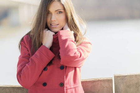 Pretty young woman in red coat photo