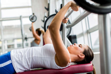 woman chest: Young woman training in the gym Stock Photo