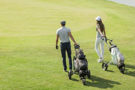 golf field: Young couple playing golf