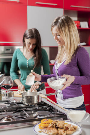 cook house: Young women in the kitchen Stock Photo
