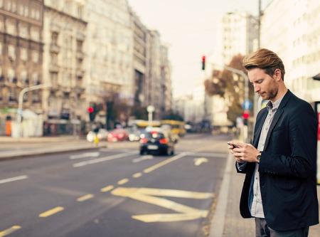 Hombre joven en la calle con el teléfono móvil