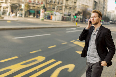 Young man on the street with mobile phone photo