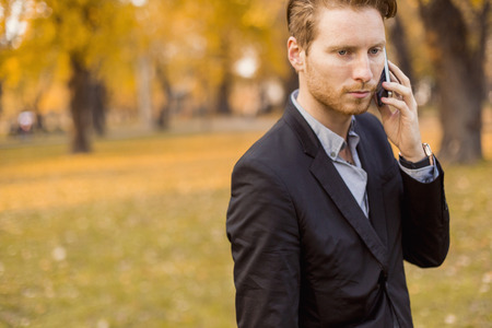 Young man with mobile phone in the autumn park photo