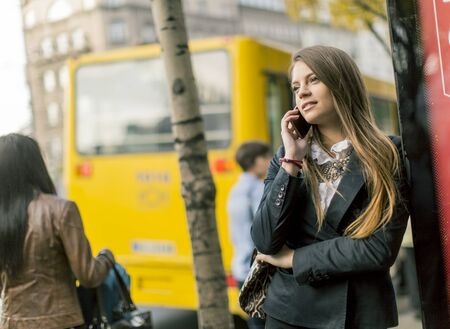 women talking: Pretty young woman talking on the mobile phone on the city street