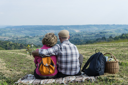 Senior couple sitting in the field photo