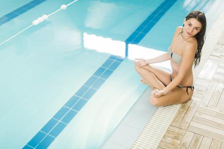 mujer meditando: Bastante joven mujer meditando en la piscina Foto de archivo