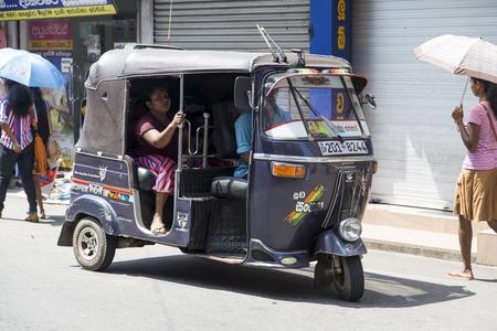 bajaj: GALLE, SRI LANKA - JANUARY 24, 2014: Unidentified people at auto rickshaw or tuk-tuk on the street of Galle. Most tuk-tuks in Sri Lanka are a slightly modified Indian Bajaj model, imported from India.