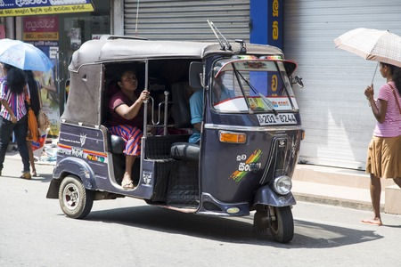 GALLE, SRI LANKA - JANUARY 24, 2014: Unidentified people at auto rickshaw or tuk-tuk on the street of Galle. Most tuk-tuks in Sri Lanka are a slightly modified Indian Bajaj model, imported from India.