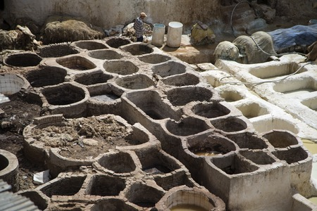 11th century: FES, MOROCCO - SEPTEMBER 15, 2014: Unidentified man working at tannery in Fes, Morocco. This is the oldest leather tannery in the world and has not changed since the 11th century. Editorial