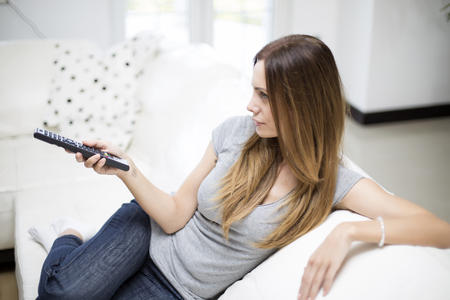 changing channels: Young woman changing channels with remote control