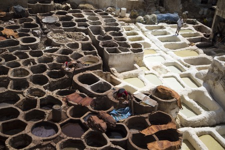 11th century: FES, MOROCCO - SEPTEMBER 15, 2014: Unidentified people working at tannery in Fes, Morocco. This is the oldest leather tannery in the world and has not changed since the 11th century.