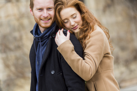 Young red hair couple at autumn park photo