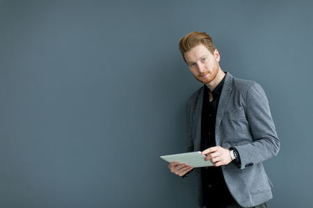 ginger hair: Young man with tablet by the wall