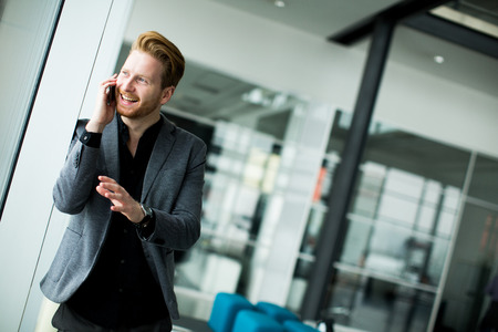Young man with mobile phone in the office photo