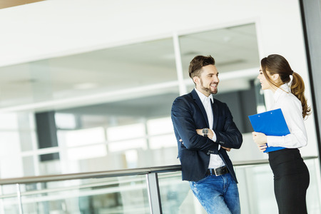 dos personas conversando: Pareja joven que trabaja en la oficina