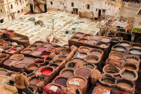 11th century: FES, MOROCCO - DECEMBER 12, 2014: Unidentified people working at tannery in Fes, Morocco. This is the oldest leather tannery in the world and has not changed since the 11th century.