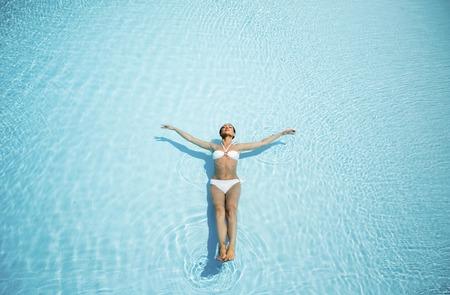 descansando: Mujer joven relajándose en la piscina