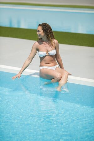 leasure: Young woman relaxing by the pool