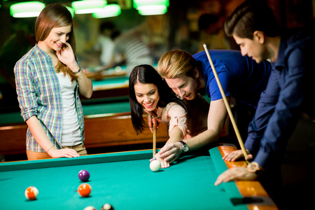 pool table: Young people playing pool