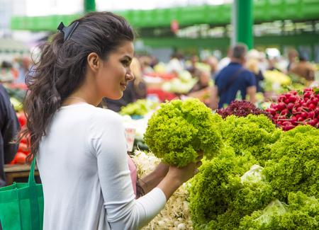 꽤 젊은 여자는 시장에서 야채를 구입