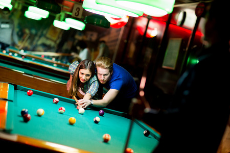 teaching adult: Young couple playing pool