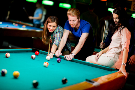 cue sticks: Young people playing pool