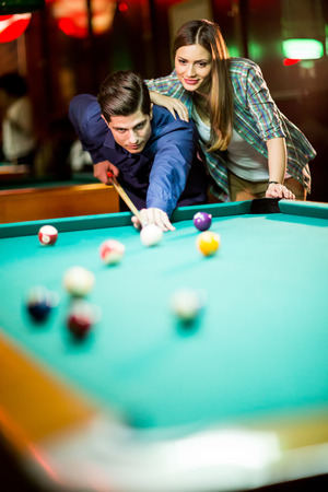 cue sticks: Young couple playing pool